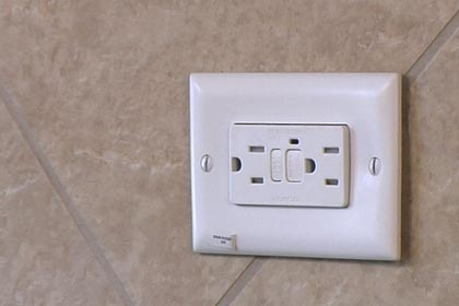 What could be causing my Christmas lights to be dim when I plug them into a GFCI plug?